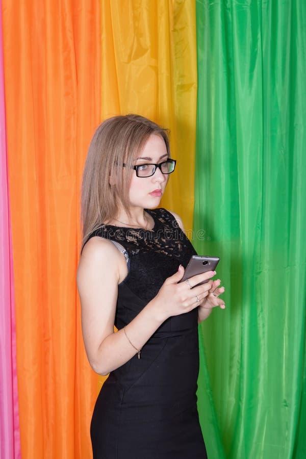 Młoda uwodzicielska dziewczyna trzyma s w czarnej sukni i okularach przeciwsłonecznych obraz royalty free