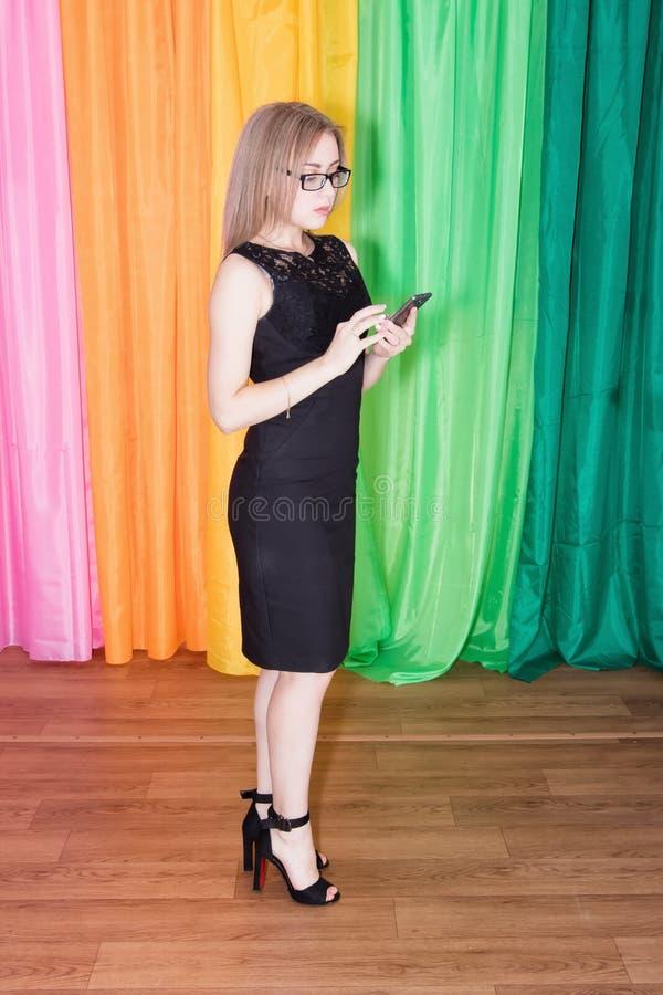 Młoda uwodzicielska dziewczyna trzyma s w czarnej sukni i okularach przeciwsłonecznych fotografia stock