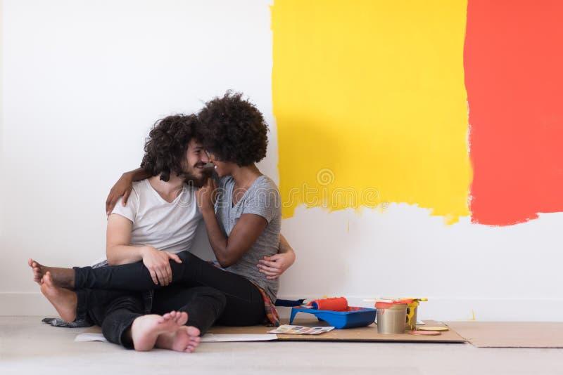 Młoda wieloetniczna para relaksuje po malować obrazy stock