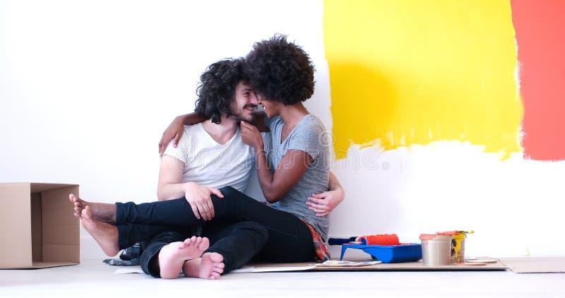 Młoda wieloetniczna para relaksuje po malować obraz royalty free