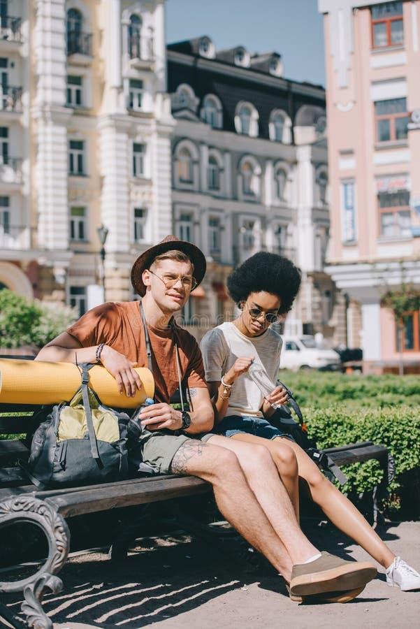 młoda wielokulturowa para turyści z butelkami wodny odpoczywać zdjęcie royalty free
