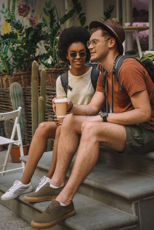 młoda wielokulturowa para z kawowym obsiadaniem fotografia royalty free