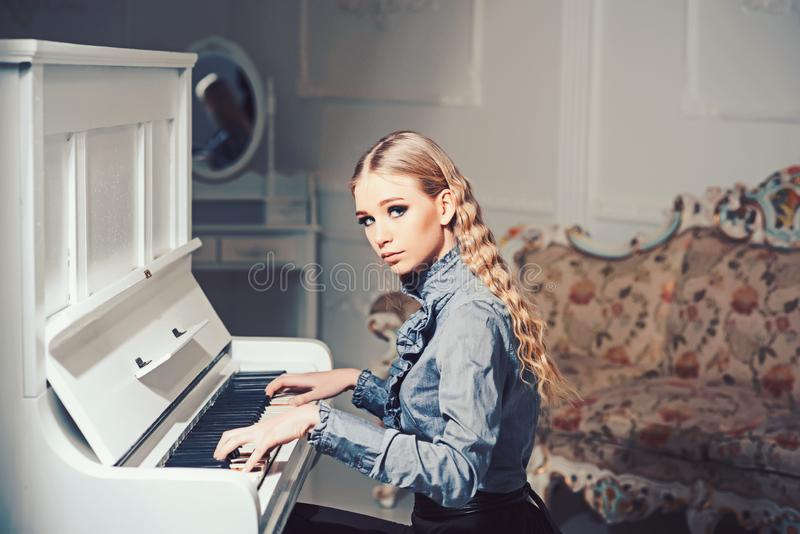 Młoda Wiktoriańska dama w czułego błękita smokingowym bawić się pianinie Uroczy blond kobiety obsiadanie w pokoju z rocznika mebl zdjęcia stock