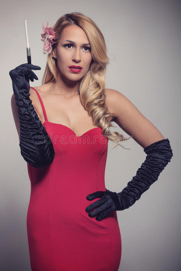 Młoda wspaniała Kaukaska blondynka w czerwieni sukni mienia papierosie obrazy stock