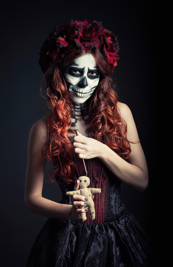 Młoda wudu czarownica z muertos makeup & x28; cukrowy skull& x29; chwyta wudu igła i lala zdjęcie stock