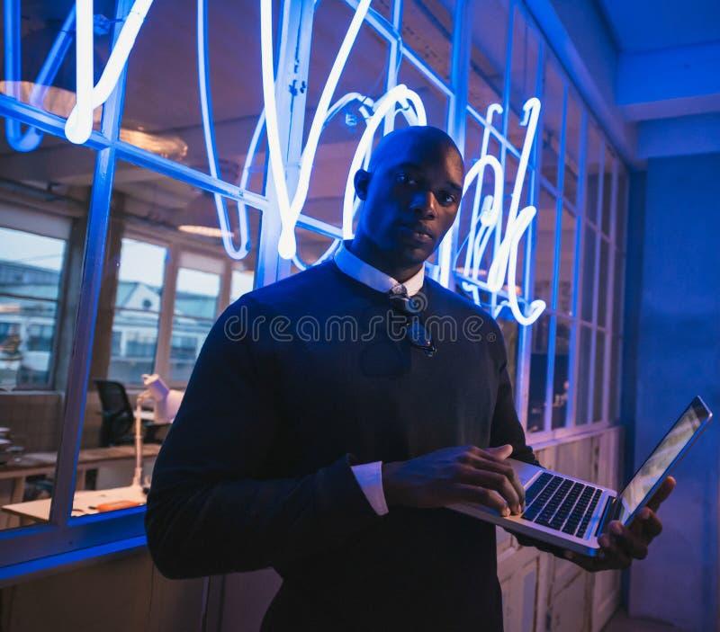 Młoda wykonawcza pozycja w biurze z laptopem zdjęcie stock