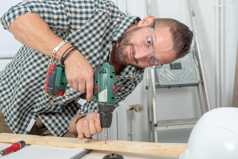 Młoda złota rączka używa elektrycznego świder, DIY w domu zdjęcie royalty free