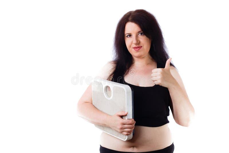 Młoda z nadwagą kobieta agituje dla zdrowego stylu życia z scal obraz royalty free