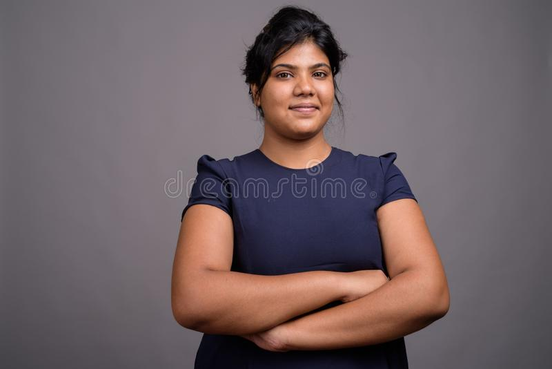 Młoda z nadwagą piękna Indiańska kobieta przeciw szaremu tłu obrazy royalty free