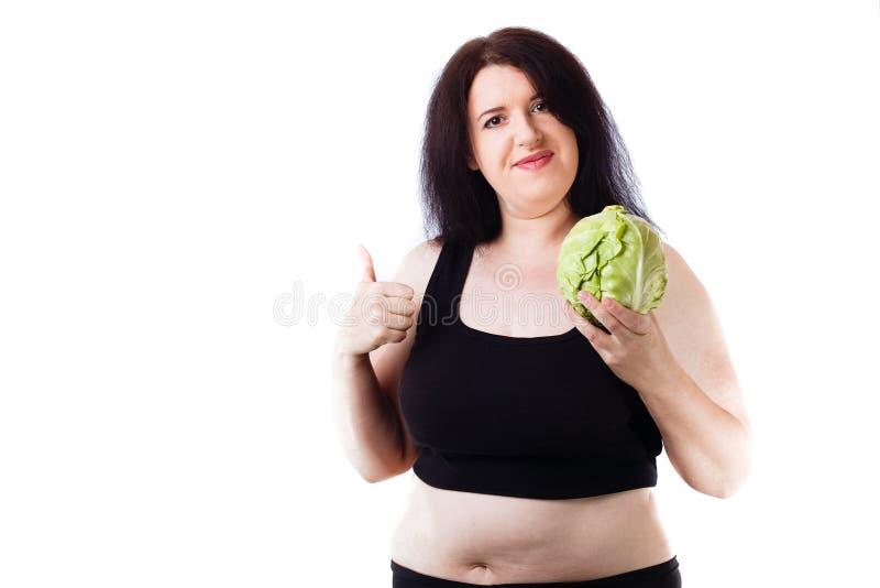 Młoda z nadwagą uśmiechnięta kobieta agituje dla zdrowego jedzenia z c fotografia royalty free