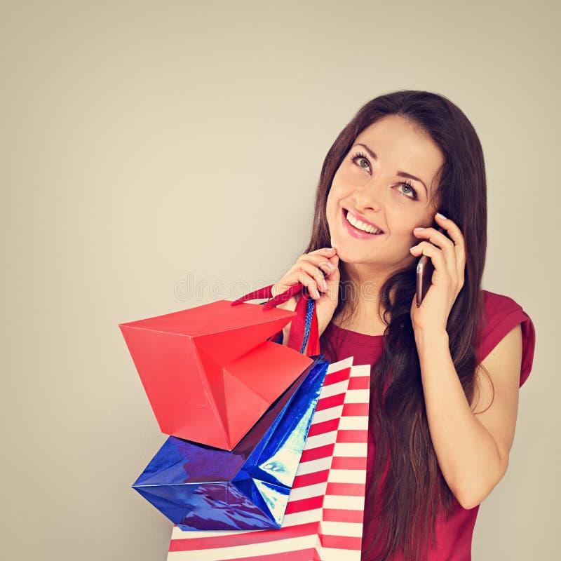 Młoda z podnieceniem toothy uśmiechnięta kobieta opowiada na telefonie komórkowym i przyglądająca w górę z torbami na zakupy zdjęcie royalty free