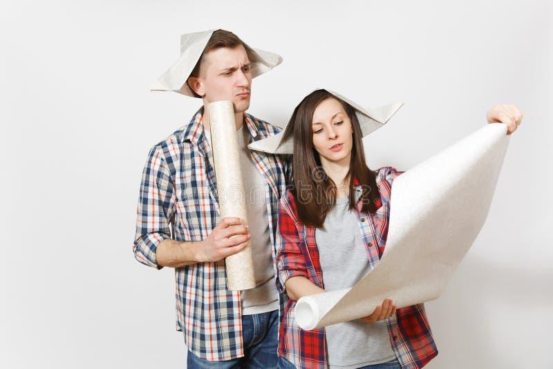 Młoda zaniepokojona kobieta, mężczyzna trzyma unrolled tapet rolki w przypadkowych ubraniach Para odizolowywająca na białym tle fotografia royalty free