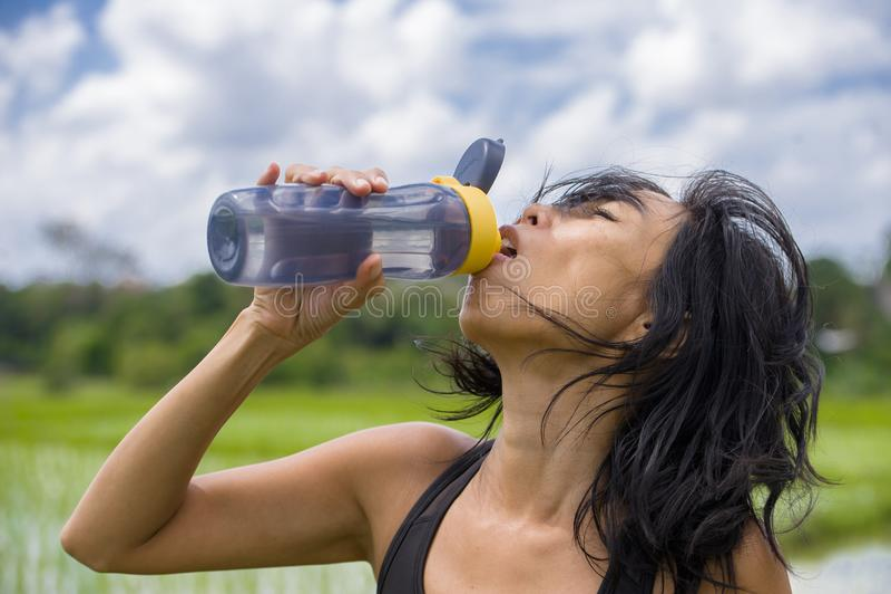 Młoda zdrowa sporty Azjatycka Chińska kobiety wody pitnej butelka po sprawność fizyczna bieg i szkolenia treningu outdoors na zie obraz stock