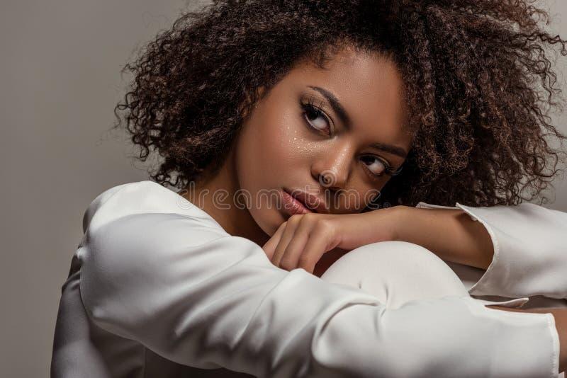 Młoda zmysłowa amerykanin afrykańskiego pochodzenia kobieta w biały koszulowy patrzeć daleko od obraz stock