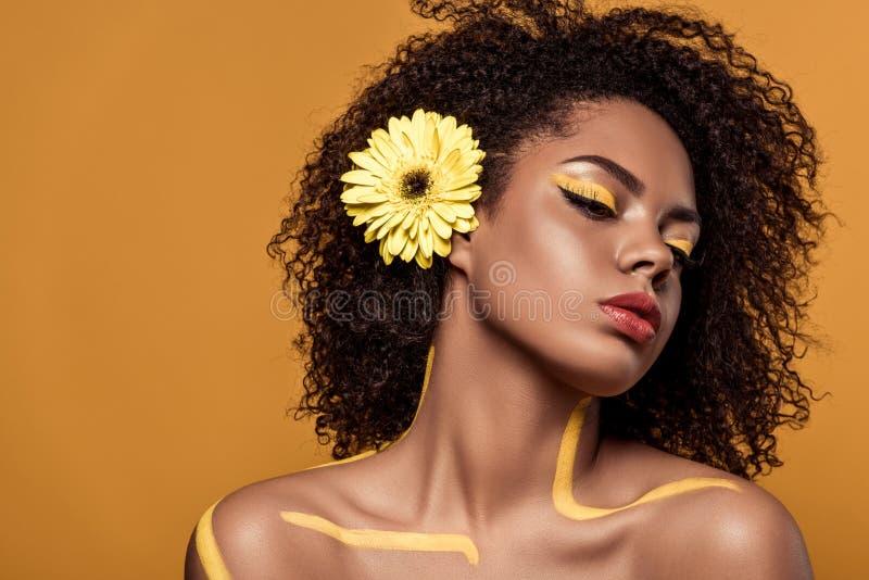 Młoda zmysłowa amerykanin afrykańskiego pochodzenia kobieta z artystycznym makijażem i gerbera w włosy zdjęcie royalty free