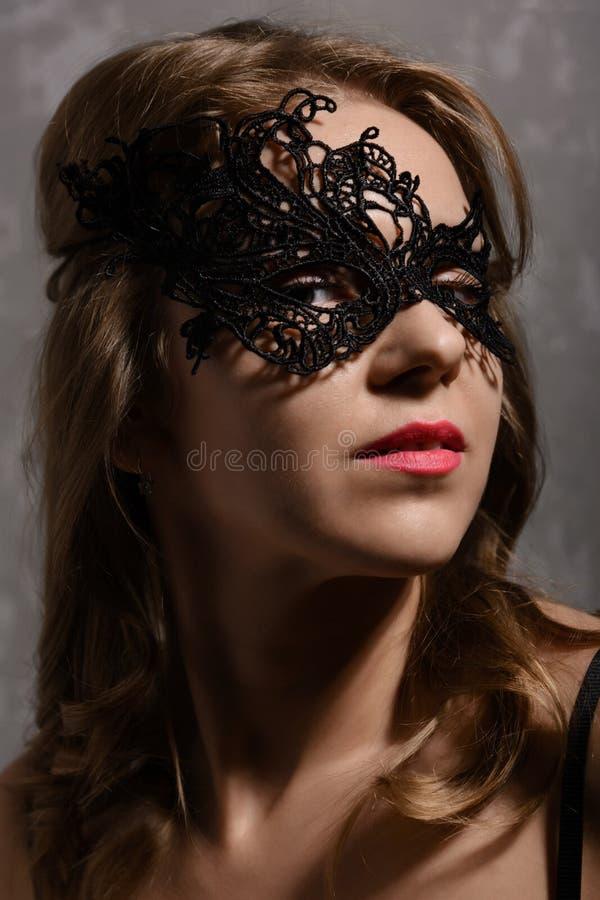 Młoda zmysłowa imbirowa kobieta jest ubranym czerni przyjęcia maskę obrazy royalty free