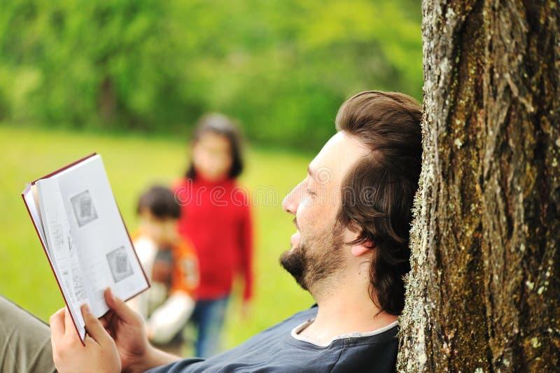 Młoda zrelaksowana ojca czytania książka obraz royalty free