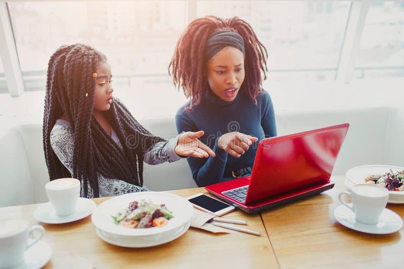Młode amerykanin afrykańskiego pochodzenia kobiety siedzą przy stołem Wskazują przy laptopem Modele udaremniają i zadziwiają Jedz zdjęcie royalty free