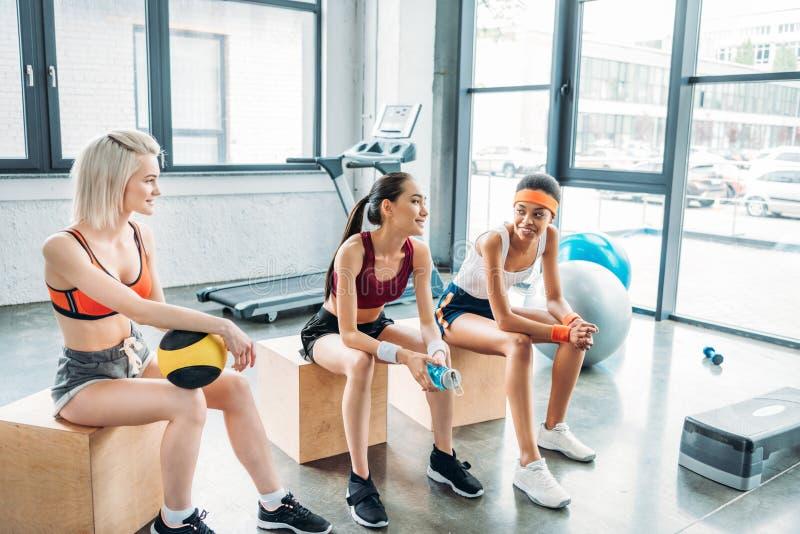 młode atrakcyjne wielokulturowe sportsmenki siedzi na drewnianych pudełkach obraz stock