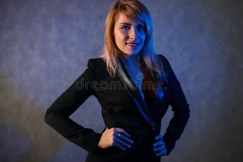Młode blondynki czerni kurtki pozy w popielatym studiu obrazy stock