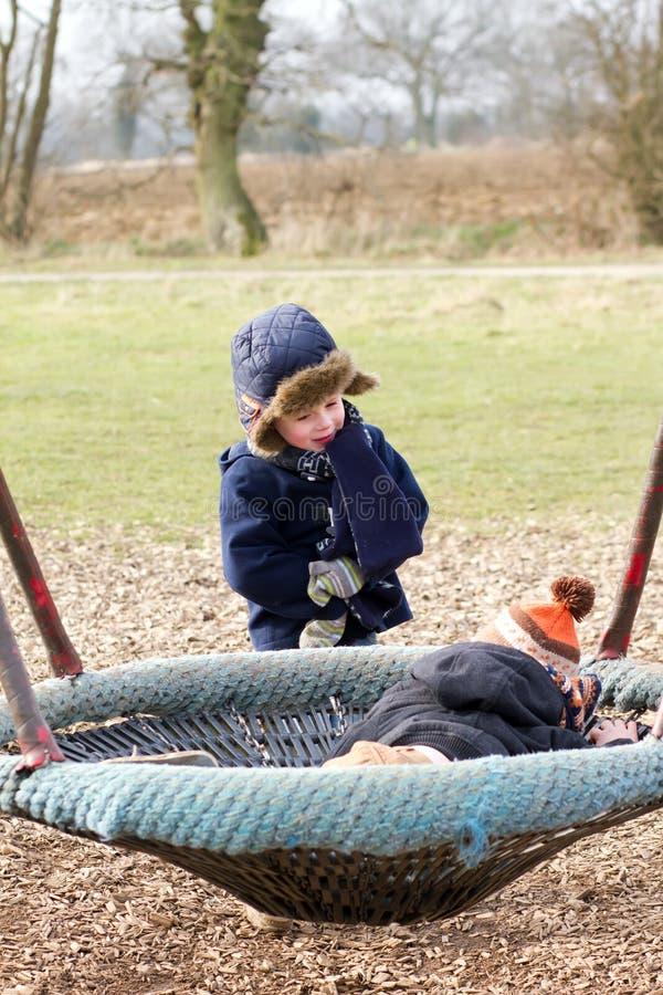 młode chłopiec bawić się przy parkiem na zimnym dniu obraz stock