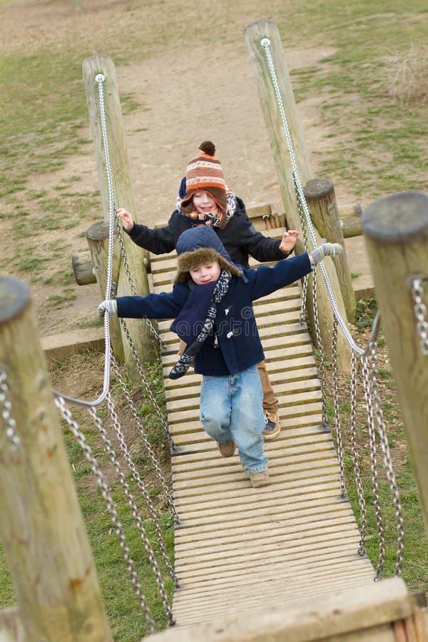 młode chłopiec bawić się przy parkiem na zimnym dniu zdjęcia stock