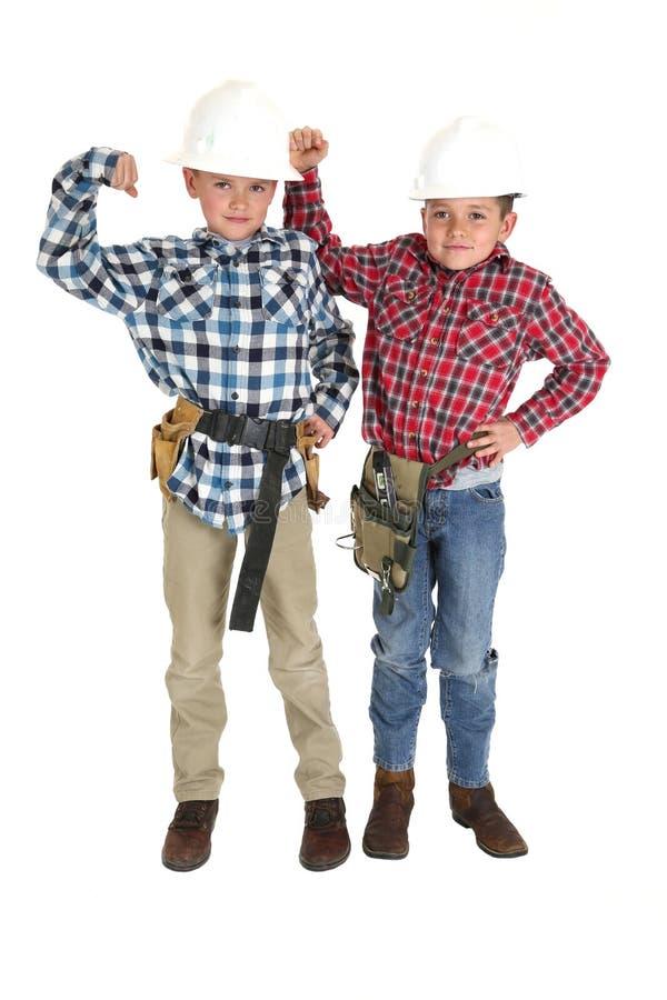 Młode chłopiec jest ubranym hardhats i narzędzie paski fotografia royalty free