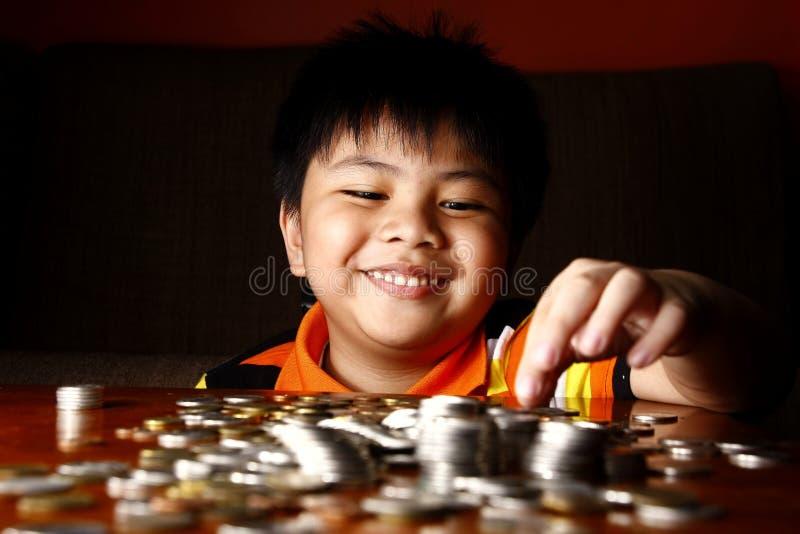Młode chłopiec palowania lub sztaplowania monety fotografia royalty free