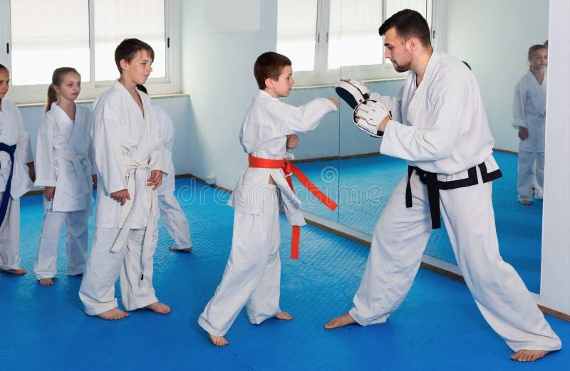 Młode chłopiec trenuje karate kopnięcia z trenerem obraz royalty free
