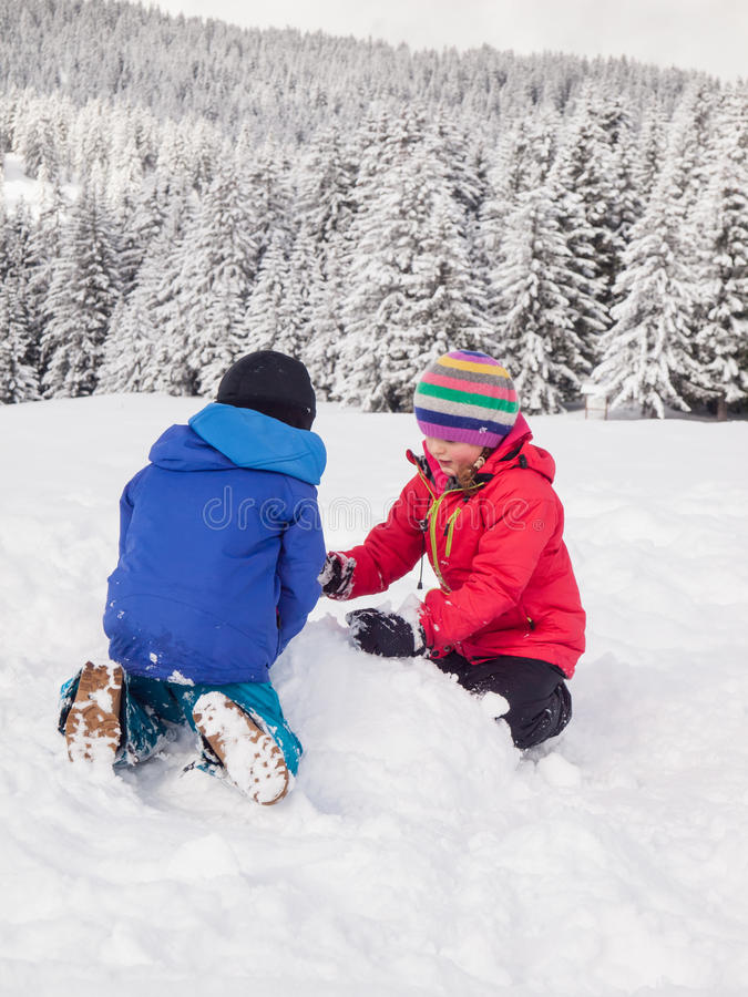 Młode dzieci bawić się w śniegu zdjęcia royalty free