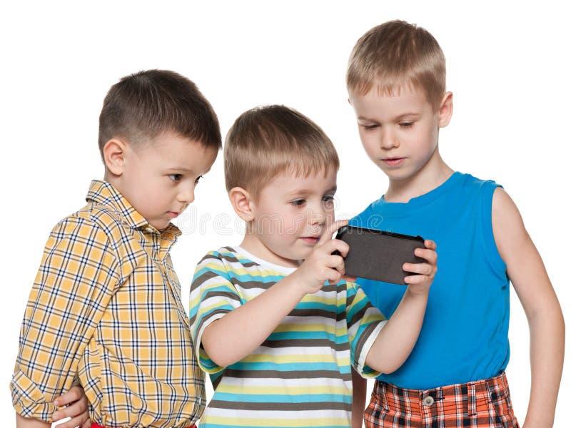 Młode dzieci plaing z nowym gadżetem fotografia royalty free