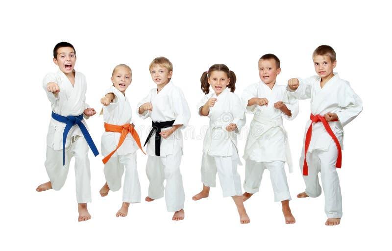 Młode dzieci w kimonie wykonują technika karate na białym tle