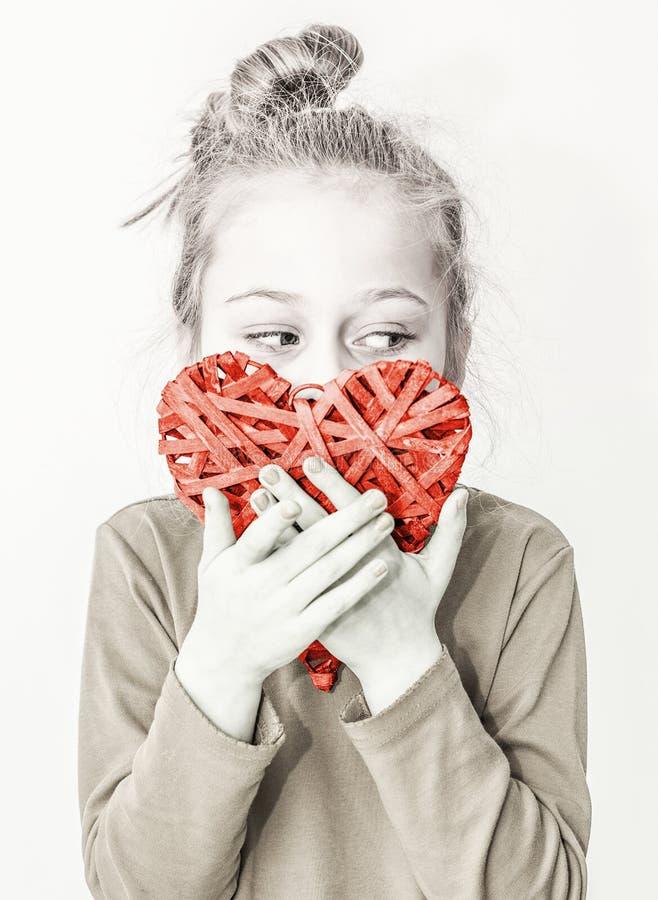 Młode dziecko dziewczyny mienia czerwony kierowy symbol - kocha pojęcie zdjęcia stock