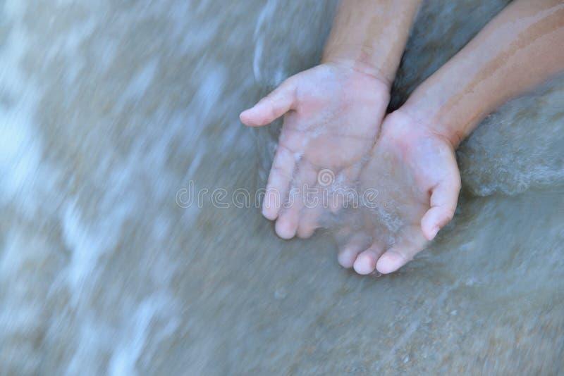 Młode dziecko ręki w nawadniają przepływ fotografia royalty free