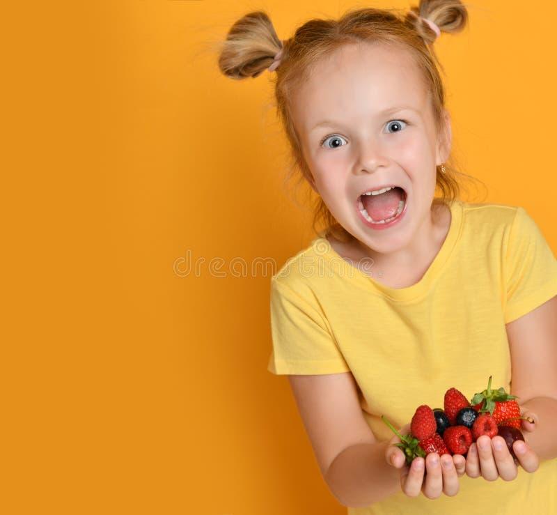 Młode dziewczynka dzieciaka chwyta jagod owoc w rękach zaskakiwali szczęśliwy śmia się krzyczeć na kolorze żółtym obrazy stock