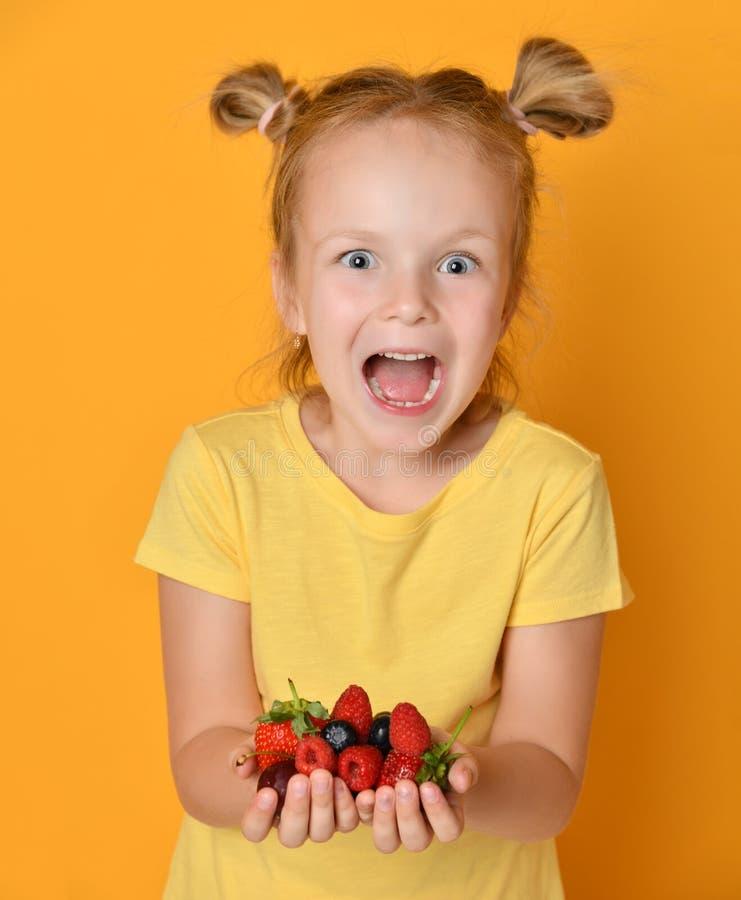 Młode dziewczynka dzieciaka chwyta jagod owoc w rękach zaskakiwali szczęśliwy śmia się krzyczeć na kolorze żółtym zdjęcie royalty free