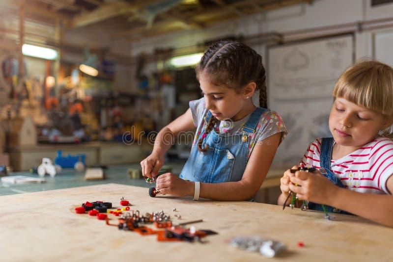 Młode dziewczyny buduje zabawkarską budowy maszynę zdjęcie royalty free