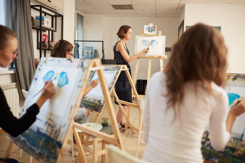Młode dziewczyny i rysunkowi nauczyciel farby obrazki siedzi przy sztalugami w sztuki studiu zdjęcia stock