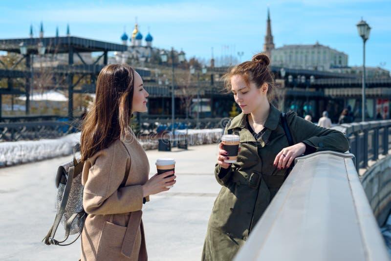 Młode dziewczyny opowiada na nabrzeżu Kazan w żakietach i kawie Przerwa zdjęcia royalty free
