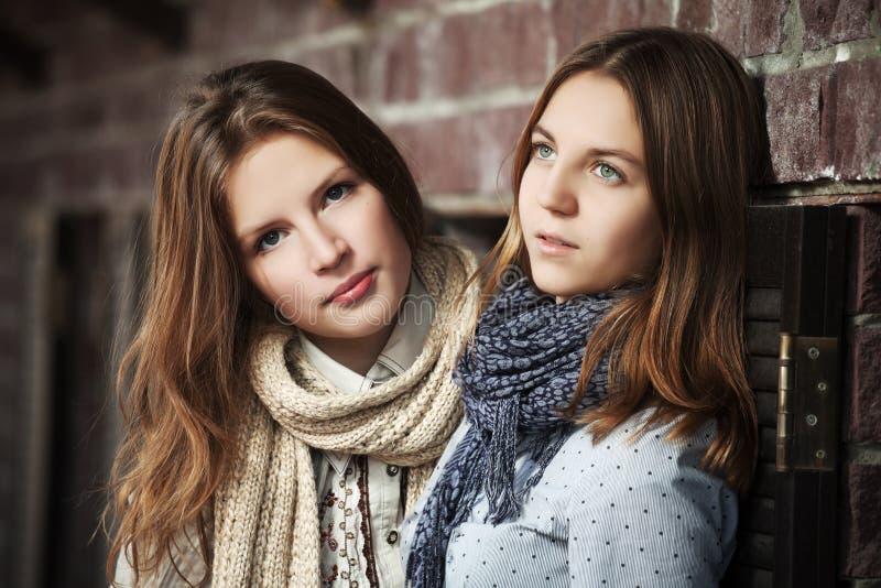 Młode dziewczyny przeciw ściana z cegieł fotografia royalty free