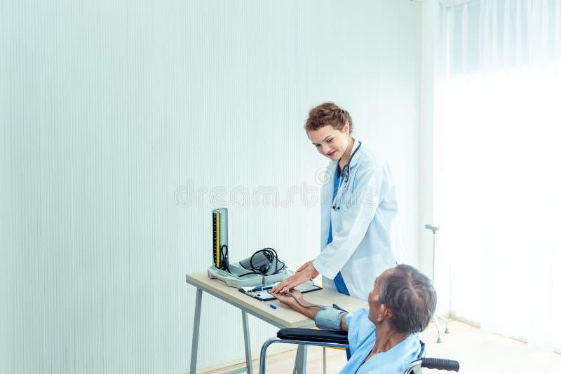 Młode fachowe kobiety lekarki pomocne dłonie, wyjaśnia diagnozę starszego mężczyzny pacjent w medycznym biurze przy hospita obraz royalty free