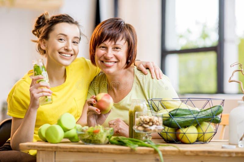 Młode i stare kobiety z zdrowym jedzeniem indoors obrazy royalty free