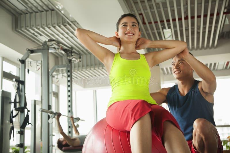 Młode kobiety ćwiczy z jej osobistym trenerem w gym obraz stock