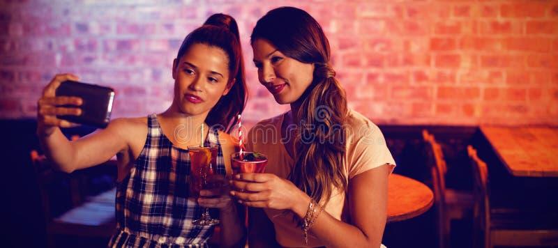 Młode kobiety bierze selfie podczas gdy mieć koktajl pije fotografia stock