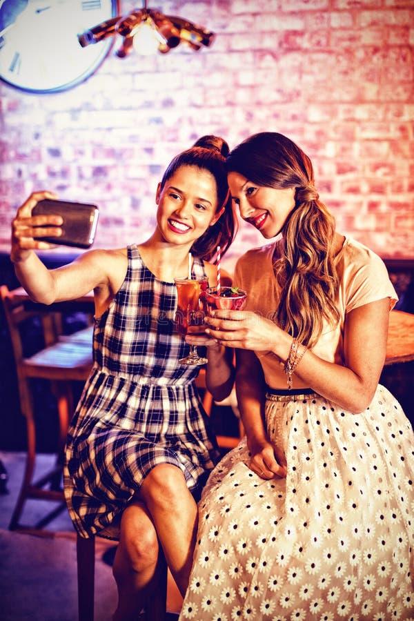 Młode kobiety bierze selfie podczas gdy mieć koktajl pije fotografia royalty free