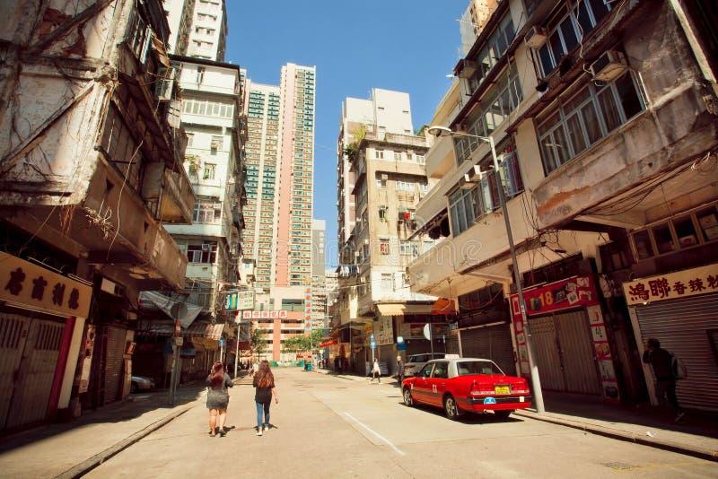 Młode kobiety chodzi za taxi taksówką na nieociosanej miasto ulicie fotografia stock