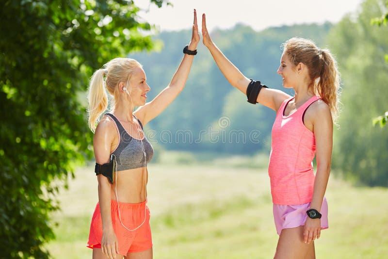 Młode kobiety daje each inny Wysocy Pięć zdjęcia stock