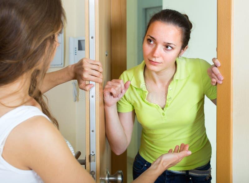 Młode kobiety ma konflikt przy drzwi obraz royalty free