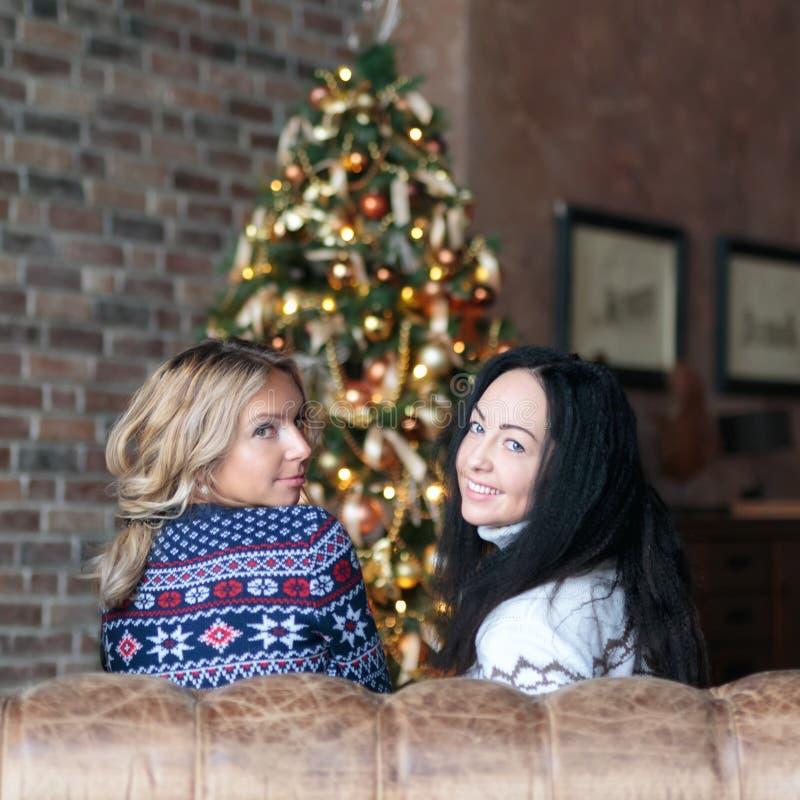 Młode kobiety ono uśmiecha się podczas gdy siedzący blisko choinki zdjęcie stock