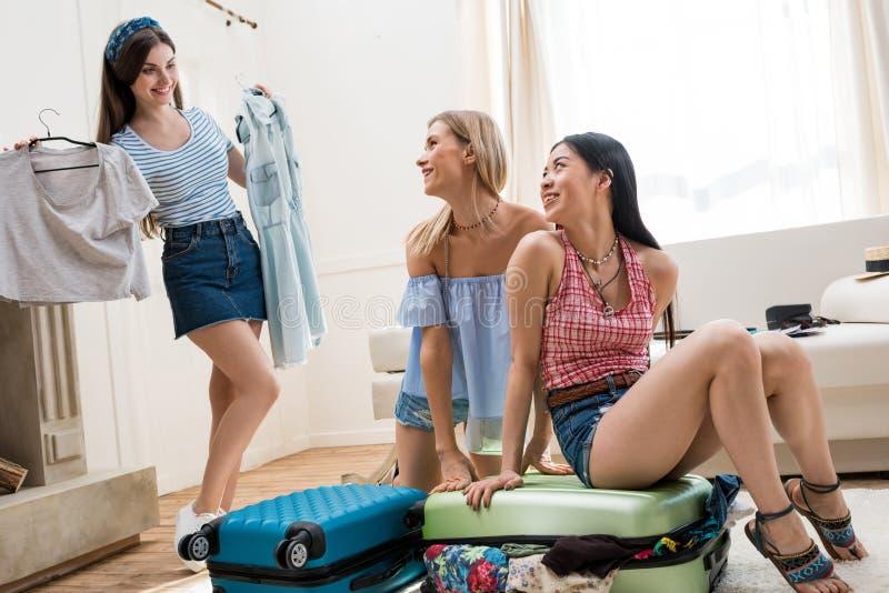 młode kobiety pakuje walizki dla wakacje podróży wpólnie w domu obrazy stock